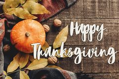 Happy thanksgiving text sign flat lay. pumpkin with leaves and. Walnuts on stylish scarf top view, space for text. seasonal greetings, autumn fall holidays stock photo