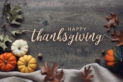 Happy Thanksgiving typography with pumpkins and leaves over dark wood background