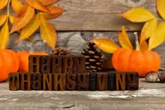 Happy Thanksgiving wooden blocks against rustic wood with autumn leaves Royalty Free Stock Photos