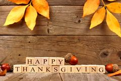 Happy Thanksgiving wooden blocks with wood background, acorns, leaves Royalty Free Stock Photos