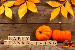 Happy Thanksgiving wooden blocks with wood background, leaves and pumpkins Stock Photo