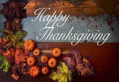 Happy Thanksgiving. On wooden vintage board with pumpkins and leaves Stock Photos