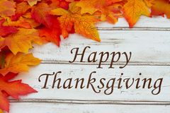 Happy Thanksgiving. Written on grunge wood background with Autumn Leaves stock photo