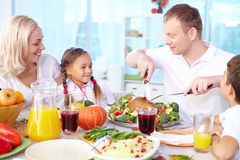 Happy Thanksgiving. Happy young family celebrating Thanksgiving by festive table Stock Photos