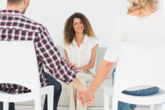 Happy therapist smiling at reconciled couple holding hands Royalty Free Stock Photography