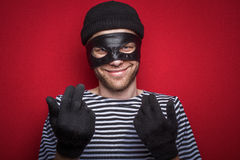 Happy thief wants your money. Classic thief standing at the red background royalty free stock photos