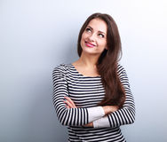 Happy thinking casual girl with folded hands looking up Royalty Free Stock Image