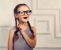 Happy thinking kid girl in fashion glasses with excited emotiona. L face looking on studio background. Closeup toned portrait Stock Photos