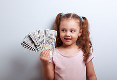 Happy thinking kid girl looking on the money in the hand and joy Royalty Free Stock Photo