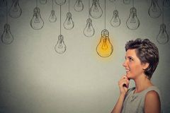 Happy thinking woman looking up with bright light idea bulb above head Royalty Free Stock Images