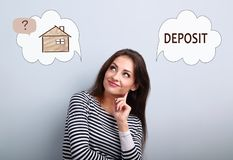 Happy thinking woman looking up and thinking deposit or buying t. O house. Concept illustration with house in bubble cloud and deposit word. Investment to safety royalty free stock images