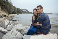 Happy thoughtful couple sitting on a rock beach near sea hugging Royalty Free Stock Photography