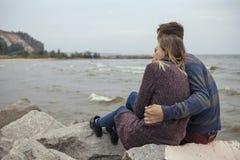 Happy thoughtful couple sitting on a rock beach near sea hugging Stock Image