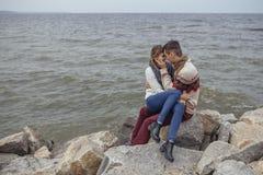 Happy thoughtful couple sitting on a rock beach near sea hugging stock photo