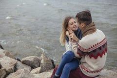 Happy thoughtful couple sitting on a rock beach near sea hugging stock photos