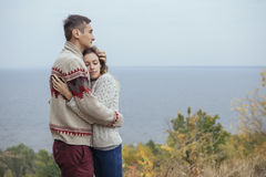 Happy thoughtful couple standing on a cliff near sea hugging eac Stock Images
