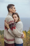 Happy thoughtful couple standing on a cliff near sea hugging each other in cold foggy cloudy autumn weather. Copy space royalty free stock image