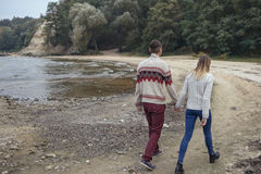 Happy thoughtful couple standing on a rock beach near sea hugging each other in cold foggy cloudy autumn weather. Copy space stock photos