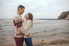 Happy thoughtful couple standing on a rock beach near sea hugging each other in cold foggy cloudy autumn weather. Copy space royalty free stock photography