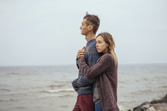 Happy thoughtful couple standing on a rock beach near sea hugging each other in cold foggy cloudy autumn weather. Copy space stock image