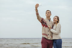 Happy thoughtful couple standing on a rock beach near sea hugging each other in cold foggy cloudy autumn weather. Man photograph royalty free stock photography