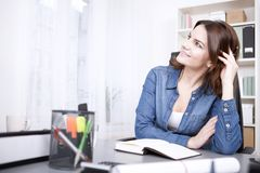 Happy Thoughtful Office Woman Leaning on the Table. Close up Happy Thoughtful Office Woman Leaning on the Table with Pen and Book, Looking to the Upper Left of Royalty Free Stock Image