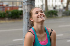 Happy Thoughtful Sporty Woman Leaning Against Post. Close up Thoughtful Sporty Young Woman Leaning Against the Post at the Street with a Happy Face and Eyes are Royalty Free Stock Image