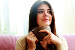 Happy thoughtful woman holding cup of coffee Stock Photo