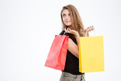 Happy thoughtful woman holding shopping bags Stock Photo