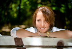 Happy Thoughtful Woman Leaning on a Wooden Bench Stock Photos