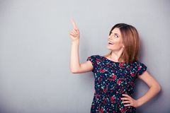 Happy thoughtful woman pointing finger up Stock Image