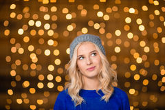 Happy thoughtful woman standing over holidays lights background Royalty Free Stock Photo