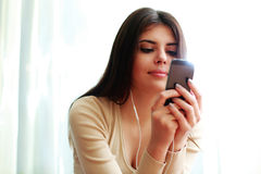 Happy thoughtful woman using smartphone Stock Photo