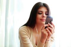 Happy thoughtful woman using smartphone Stock Photo