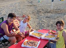 Happy three brothers eating pizza on the beach Stock Photography