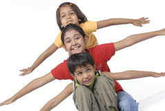 Happy three children. Three children sitting with arms outwards Royalty Free Stock Images