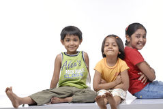 Happy three children. Brother and two sisters sitting in the studio Stock Photo