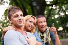 Happy three friends. Group of stylish friends in a park on summer day royalty free stock image