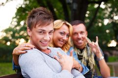 Happy three friends. Group of stylish friends in a park on summer day stock photo
