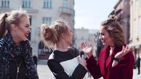 Happy three friends wandering in the old city center, laughing, and joking. The woman in a red coat hugs her friend