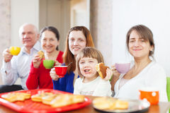 Happy family drinks tea with cakes Royalty Free Stock Image