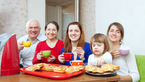 Happy family drinks tea and eats cakes Stock Photos