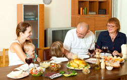 Happy three generations family eating chicken over big table Royalty Free Stock Photos