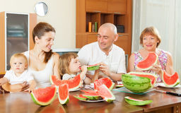 Happy three generations family eating  melon Stock Photos