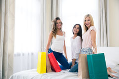 Happy three girlfriends with shopping bags Royalty Free Stock Photo