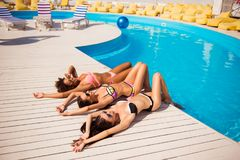 Happy three girls sun bathing near the pool. Attractive skinny g royalty free stock photography