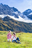 Happy three kids in field between snow mountains Royalty Free Stock Photos