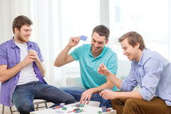 Happy three male friends playing poker at home Royalty Free Stock Image