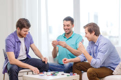 Happy three male friends playing poker at home Stock Images