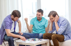 Happy three male friends playing poker at home Royalty Free Stock Photos